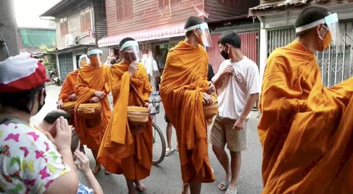 Monjes budistas en Bangkok salen a recibir limosna con mascarillas por el coronavirus