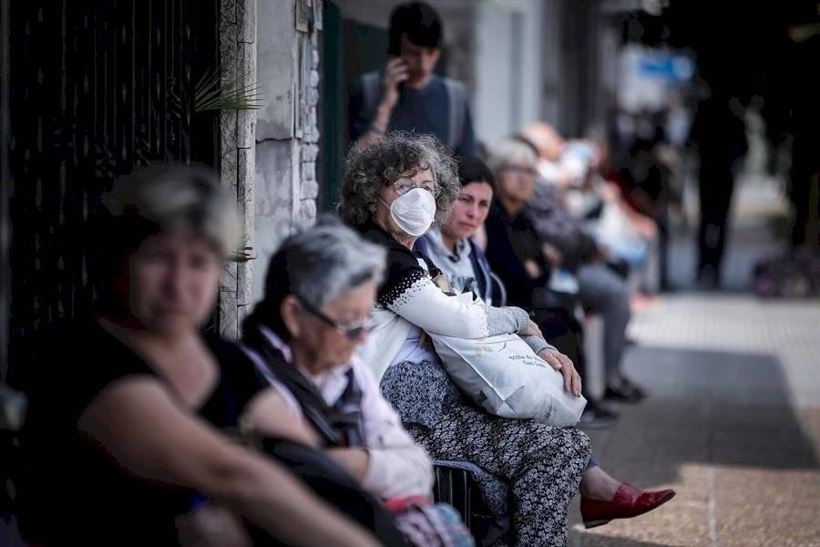 Personas que hacen fila afuera de un banco donde pagan jubilaciones y planes sociales este viernes, en Buenos Aires. EFE/Juan Ignacio Roncoroni