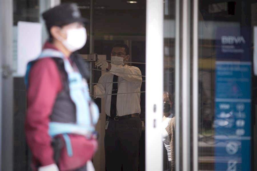 Un hombre cierra la puerta de un banco donde pagan jubilaciones y planes sociales este viernes, en Buenos Aires. EFE/Juan Ignacio Roncoroni
