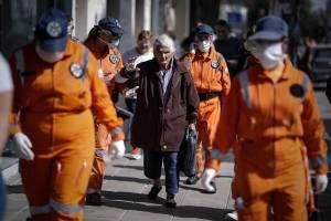 Paramédicos caminan frente a personas que hacen fila afuera de un banco