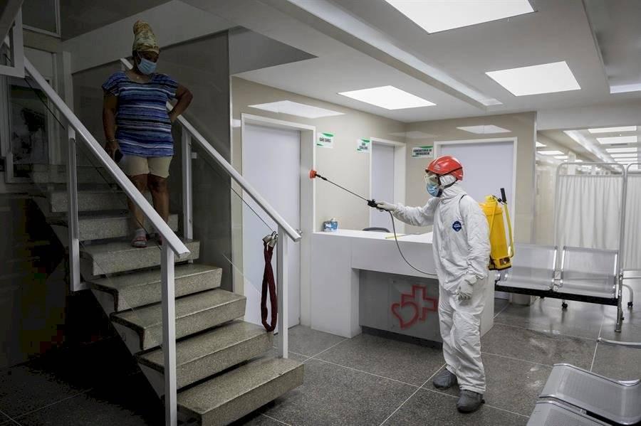 """Un miembro de Protección Civil desinfecta un hospital comunitario de buses el 6 de abril de 2020 en Caracas (Venezuela). No hay arma mala ni buena. Las armas, sin una mano que dispare, son inofensivas. Como las """"ballenas"""" de Caracas, esas máquinas monstruosas que se usan para dispersar manifestaciones a base de chorros de agua a presión, con fuerza para derribar a varias personas a la vez. EFE/Rayner Pena R"""