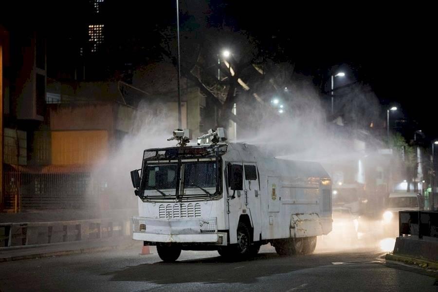 """Un vehículo de Protección Civil desinfecta una calle el 6 de abril de 2020 en Caracas (Venezuela). No hay arma mala ni buena. Las armas, sin una mano que dispare, son inofensivas. Como las """"ballenas"""" de Caracas, esas máquinas monstruosas que se usan para dispersar manifestaciones a base de chorros de agua a presión, con fuerza para derribar a varias personas a la vez. EFE/Rayner Pena R"""