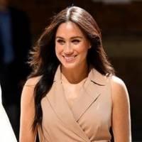 Meghan Markle luce cómoda y elegante en un vestido de mezclilla con un maxi cárdigan blanco