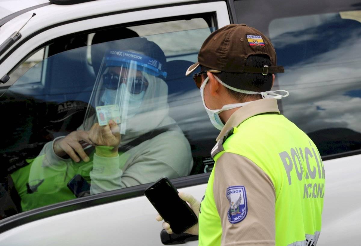 Agentes de la Policía Nacional revisan este domingo los documentos de conductores, en un puesto control en una de las avenidas del norte de Quito