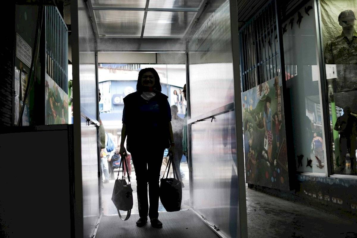 Ciudadanos ingresan este jueves a una cabina desinfectante, la primera que se coloca en el país costarricense, para prevención contra la COVID-19, en el mercado central de San José