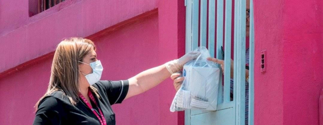 Una empleada del Fondo Costarricense de Seguridad Social (CCSS) usa una máscara facial mientras entrega medicamentos en los hogares de las personas