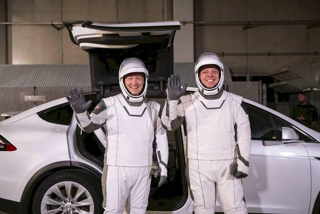 Los astronautas Doug Hurley (izquierda) y Robert Behnken posan frente al automóvil eléctrico Model X de Tesla durante un ensayo de lanzamiento en el Centro Espacial Kennedy, en Cabo Cañaveral, Florida.