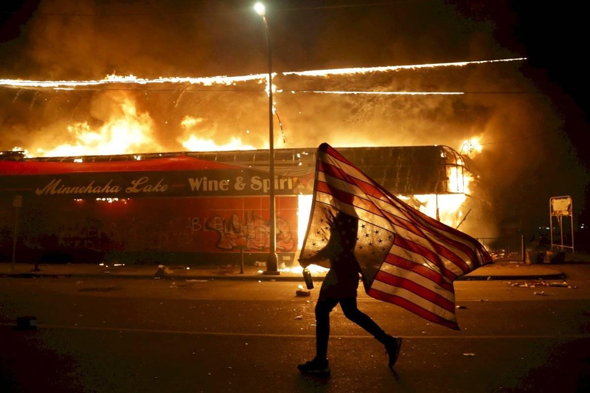 Un manifestante lleva una bandera estadounidense al revés, un signo de angustia, junto a un edificio en llamas el jueves 28 de mayo de 2020 en Minneapolis