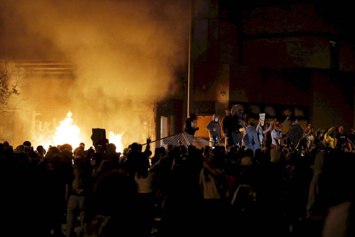 Manifestantes se concentran frente a una comisaría en llamas en Minneapolis, 28 de mayo de 2020.