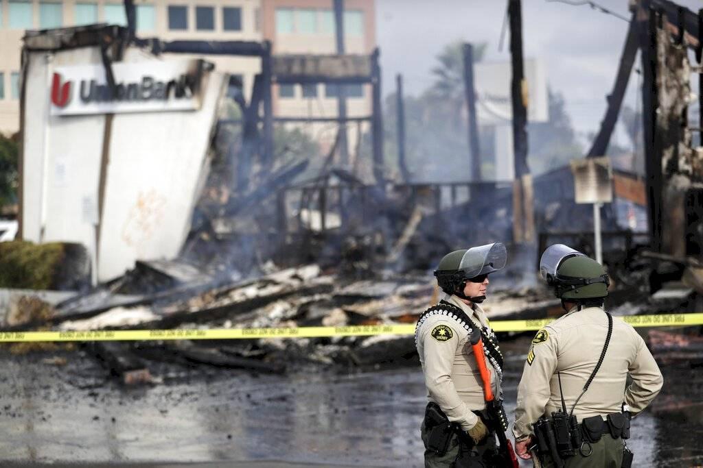 Policías del condado San Diego montan guardia el domingo 31 de mayo de 2020 frente a una sucursal bancaria quemada en La Mesa, California, después de una protesta por la muerte de George Floyd en Minneapolis. Foto: AP/ Gregory Bull