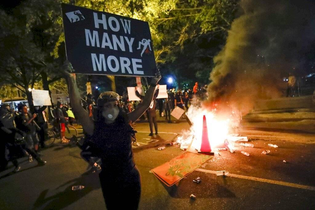 """Manifestantes protestan en Washington el domingo 31 de mayo de 2020, cerca de la Casa Blanca, por la muerte de George Floyd, quien falleció a manos de la policía en Minnesota. El letrero dice: """"¿Cuántos más?"""" Foto: AP /Alex Brandon"""