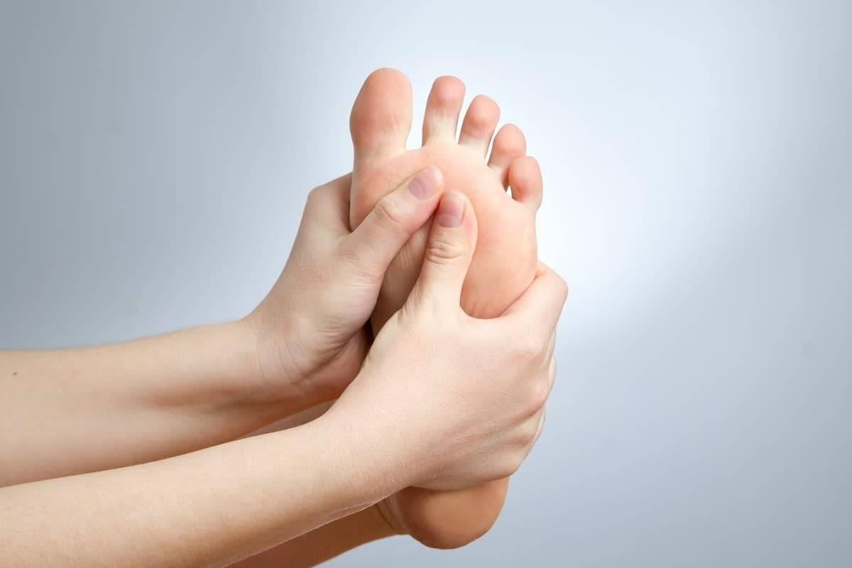 Masajea los pies con una crema hidratante