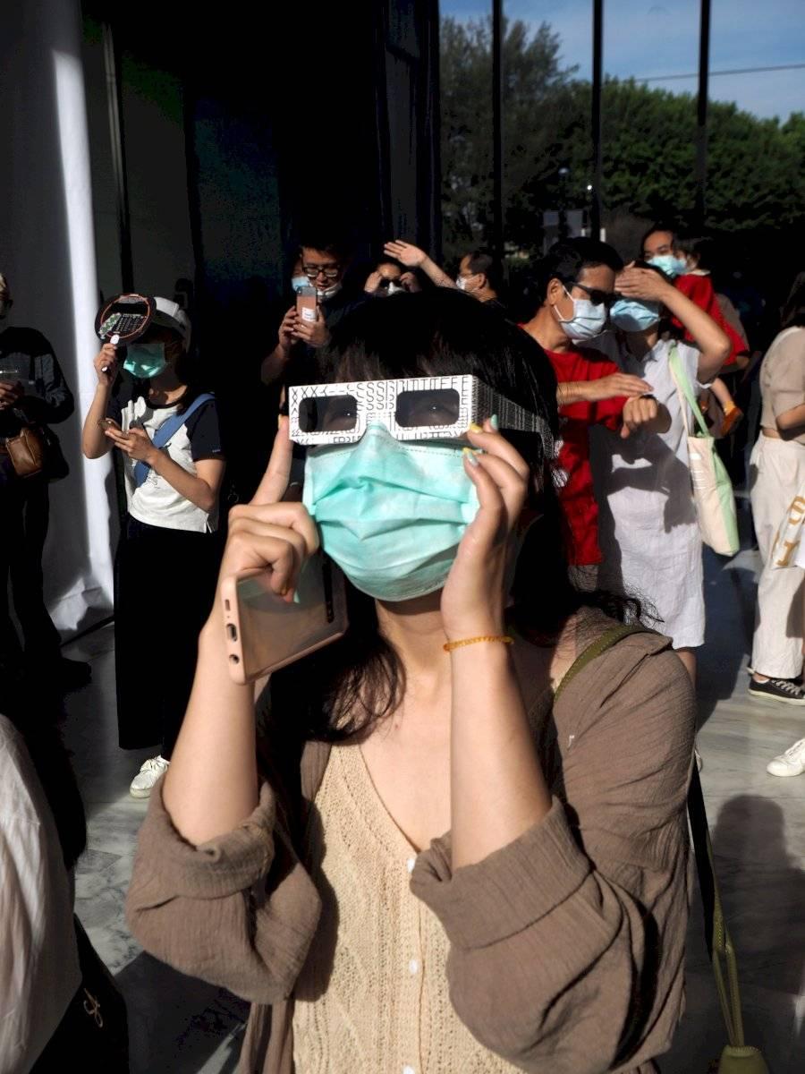 Una mujer ve el sol usando gafas protectoras especiales durante un eclipse solar anular parcial en Taipei, Taiwán, el 21 de junio de 2020