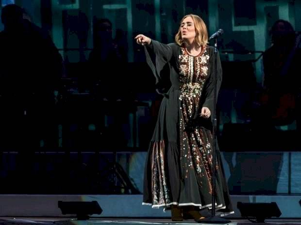 Adele falls in love with her dress in transparency and sequin and announces that there will be a new album in September