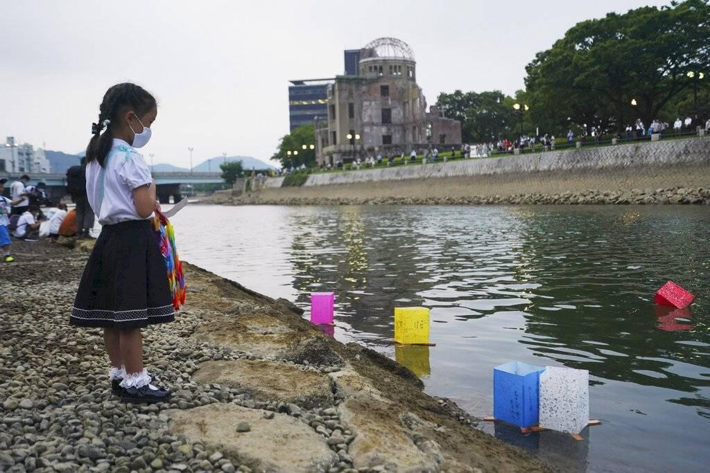 Saki Morioki, de 5 años, observa las linternas de papel que flotan a lo largo del río Motoyasu frente a la Cúpula de la Bomba Atómica. El evento oficial de las linternas fue cancelado debido al Covid-19