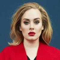 Adele hechiza con blusón de pliegos y medias de malla negra con suecos de madera