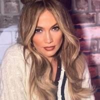 Jennifer Lopez hermosa en un pantalón de mezclilla a la cadera y mini top tejido modelando los zapatos de su colección