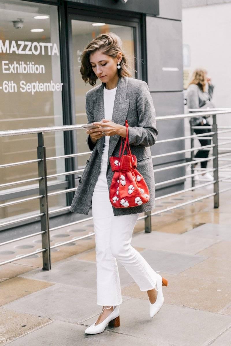 Con chaqueta larga formal color gris, blusa blanca y zapatos de tacón grueso