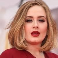 Adele luce hermosa con un pantalón palazzo, top negro y maxi abrigo rojo de flecos