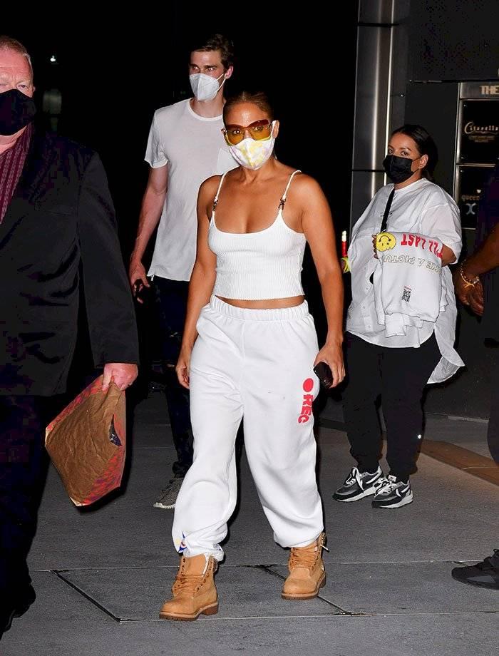 Jennifer Lopez con sus botas de obrero, combinadas con una camiseta de tiras finas y pants.