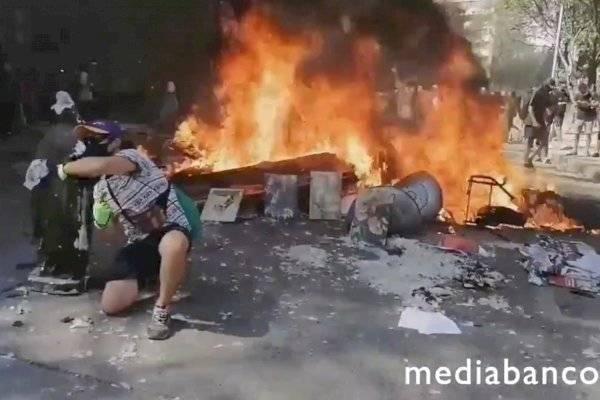 Manifestantes posan y se toman fotos junto a figuras religiosas calcinadas tras incendio de la Iglesia de Carabineros