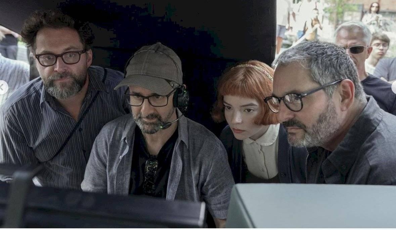 Productores y elenco juntos viendo el resultado de las escenas.
