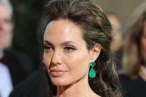 Angelina Jolie elige el blanco para deslumbrar en un vestido escotado de seda con plumas de avestruz