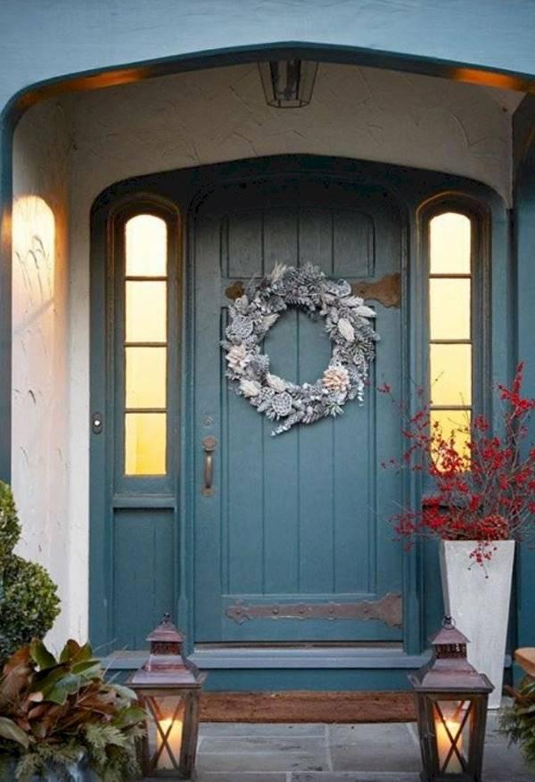 Cuelga las ramas y piñas en la puerta de entrada sin dañarla.