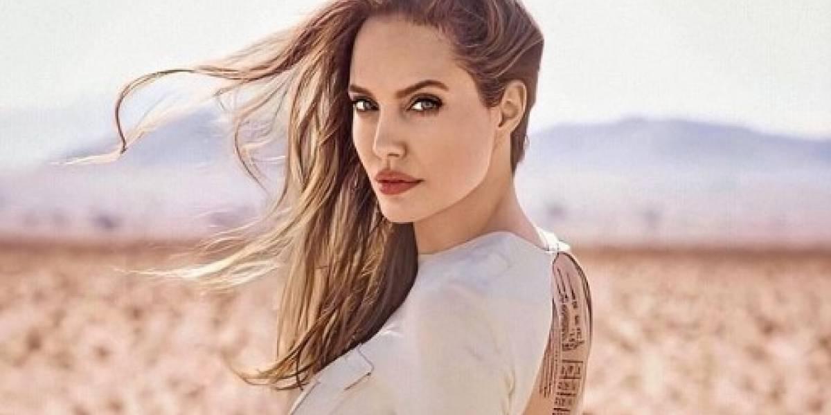 Angelina Jolie cautiva en blusa de satén blanca y falda lápiz negra, un look clásico
