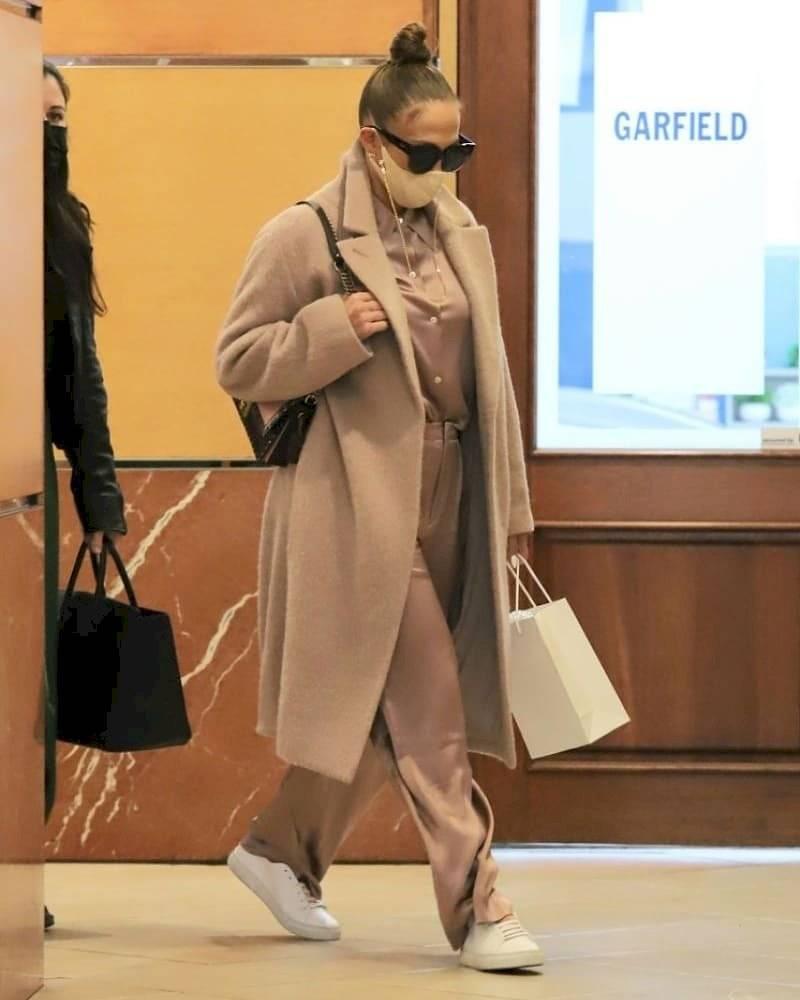 Jennifer Lopez viste seda lavanda con un abrigo largo de lana, después de conocerse actuará en la gala de Nochevieja en Times Square.
