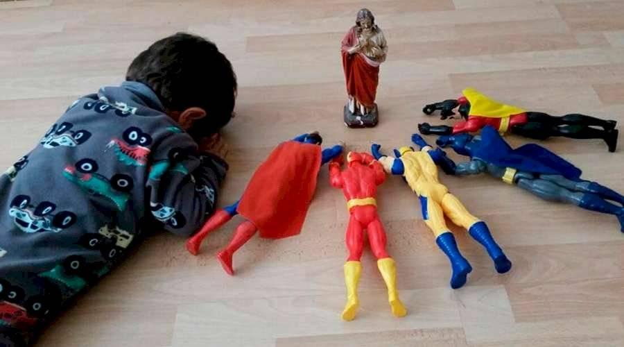 Niño reza junto a sus súperheroes