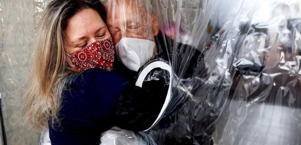"""Hija abraza a su padre con Covid-19 separados por una """"cortina"""" y la imagen se vuelve viral"""