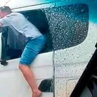 Bizarro: Caminhoneiro é flagrado com corpo para fora do caminhão e garrafa na mão